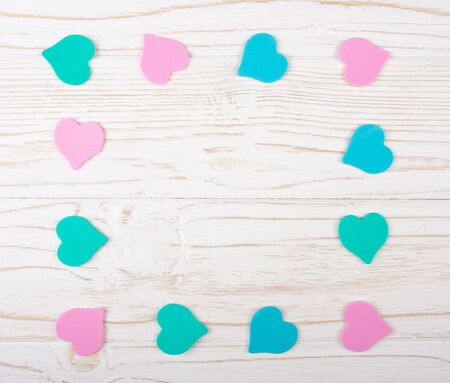 Paper hearts of pastel colors forming a frame on the white wooden background (flat lay, copy space in the center for your text)