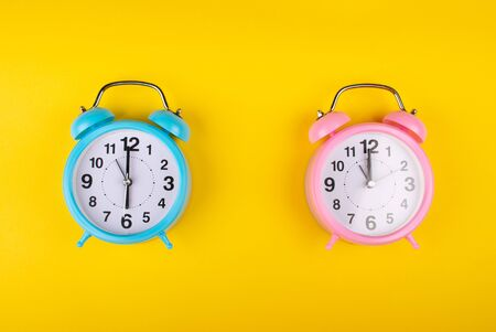 Two alarm clocks on a bright yellow background showing different time as the concept of a morning person and a night owl Stockfoto