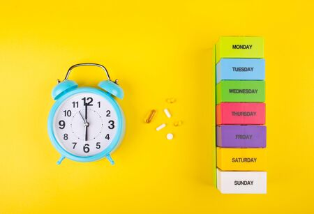 Blue alarm clock, pills and a multicolored weekly pill organizer as the Time to Take Pills concept (against a bright yellow background, flat lay)