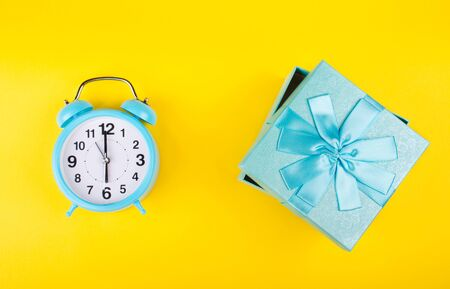Blue alarm clock and a blue gift box as the Gift Time concept (against a bright yellow background, flat lay) Stockfoto