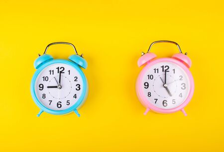 Two alarm clocks on a bright yellow background showing different time as the concept of the start and end of the working day