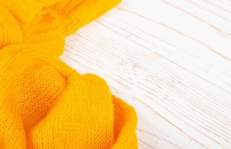 Closeup of bright yellow knitted wool on a white wooden background Standard-Bild