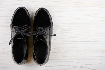 Pair of black patent leather shoes on a white wooden background (top view, copy space on the right for your text)