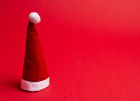 Santa hat on the bright red background as the Christmas concept (minimal style), copy space on the right for your text