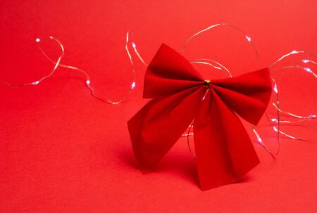 Red Christmas bow and a garland with Christmas lights on the bright red background as the Christmas concept (copy space on the left for your text) Standard-Bild
