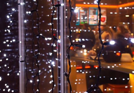 Garland with Christmas lights on a cafe window (with blurred out-of-focus silhouettes of people and Christmas decorations), selective focus