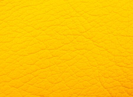 Extreme macro shot of bright yellow leather as a leather texture or an abstract yellow background