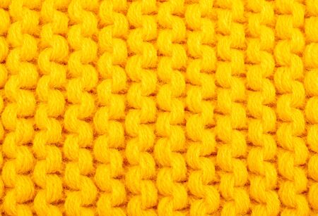 Extreme macro shot of fibers of bright yellow knitted wool (as an abstract bright yellow background)