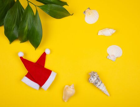 Two small Santa hats, tropical leaves and seashells on the bright yellow background as the tropical Christmas concept (copy space in the center)