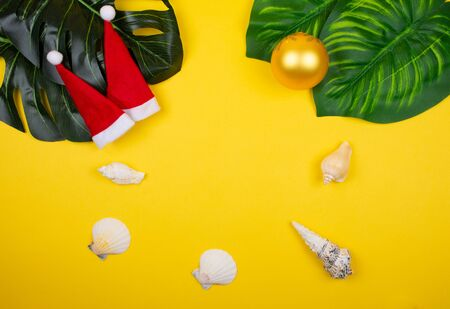 Two small Santa hats, tropical leaves, seashells and a Christmas ball on the bright yellow background as the tropical Christmas concept (copy space in the center)