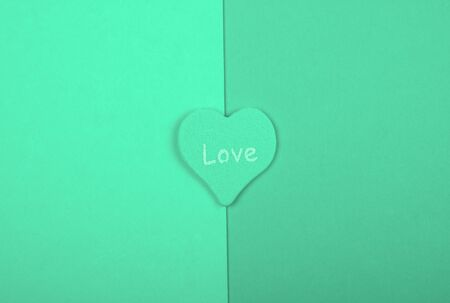 Heart with the word Love on blank pages of a book, top view, minimalist style (neo mint color)
