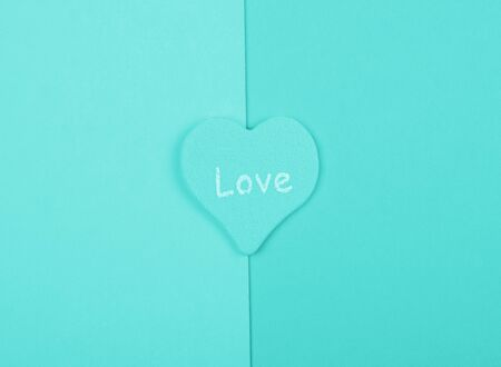 Heart with the word Love on blank pages of a book, top view, minimalist style (cyan color)
