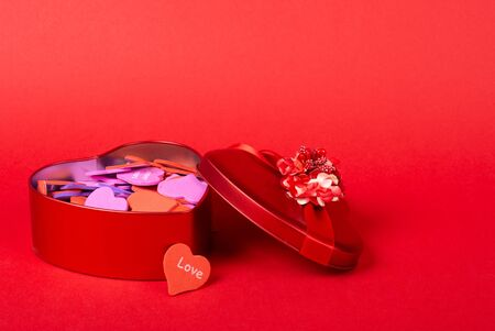 Red heart-shaped gift box with a ribbon full of multicolored handmade paper hearts on a bright red background (copy space on the right for your text, Valentine Day concept)