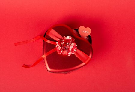 Red heart-shaped gift box with a ribbon and a handmade paper heart with the word Love on a bright red background (top view, Valentine Day or wedding concept) Standard-Bild