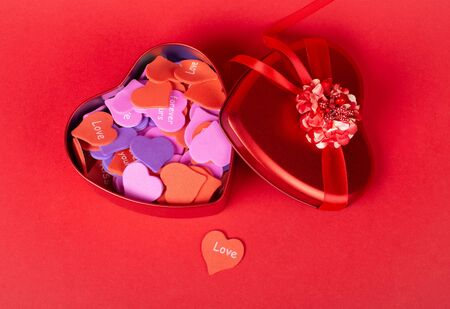 Red heart-shaped gift box with a ribbon full of multicolored handmade paper hearts and a single paper heart with the word Love on a bright red background (top view, Valentine Day or wedding concept) Stock fotó