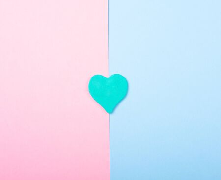 Paper heart on a split pink and blue background (top view, minimalist style)