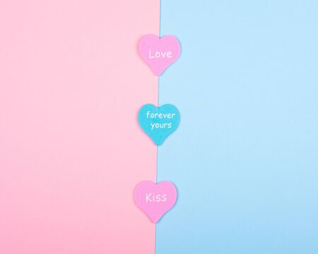 Three paper hearts with the words Love, Forever Yours and Kiss on a split pink and blue background (top view, minimalist style)