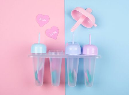 Multicolored ice cream moulds and paper hearts with the words Kiss and Love on a split pink and blue background (top view) Standard-Bild