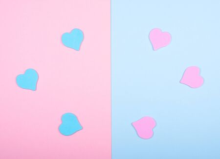 Blue and pink paper hearts on a split pink and blue background (top view, minimalist style)