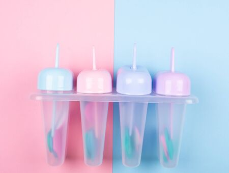 Multicolored ice cream moulds on a split pink and blue background (top view, copy space for your text)