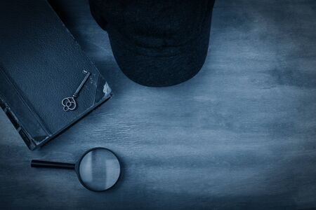 Old book, a key, a detective cap and a magnifying glass against a worn wooden background with dark edges toned in the classic blue color (top view) as the crime story concept Standard-Bild