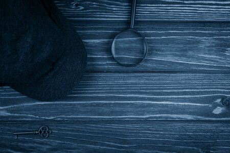 Detective cap, a key and a magnifying glass on a worn wooden background toned in the classic blue color (top view) as the private detective or investigation concept Archivio Fotografico