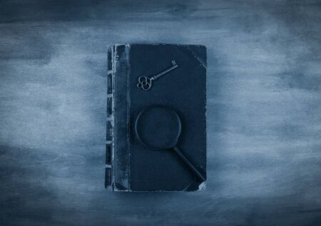 Old book, a key and a magnifying glass on the book against a worn wooden background with dark edges toned in the classic blue color (top view) as the crime story concept Standard-Bild - 141126130