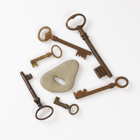 set of old rusty keys placed around gray stone with key hole on white background Banco de Imagens