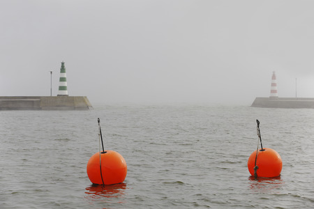 Two brant point lighthouses at harbor entrance in fog with two red bouys in the foreground, Nida, Lithuania.
