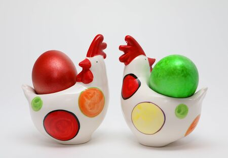 Colorful Easter eggs in two toy hens on white background, Spring Image. Easter concept. Stock fotó