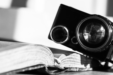 Open book and an ancient video camera. Black and white photo photo