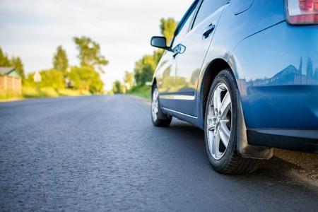 Car on asphalt road in summer evening