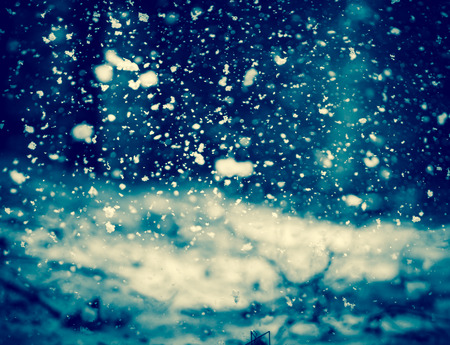 nightly: Detail of softly falling snowflakes in the nightly sky.  Blue toning.