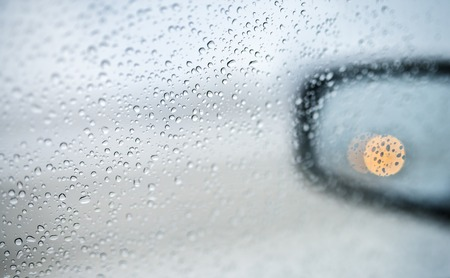 sideview: Rain drops on the side-view mirror of a car Stock Photo