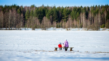 mother on bench: Mother, two little girl sitting in winter on bench with snow