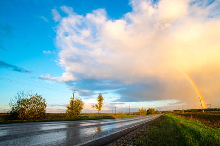 Landscape with country road and rainbow. Stock Photo