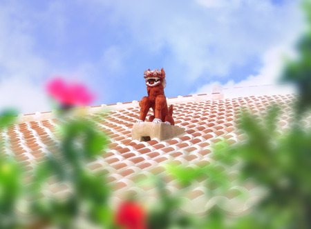 Statue of a Shisa, patron deity of Okinawa, on a red tile roof through a hedge of hibiscus.