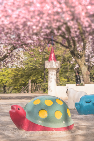 Cute red turtle and blue pig scuptures make a hanami party under the pink cherry blossom trees of Asukayama park in the Kita district of Tokyo, Japan. 에디토리얼