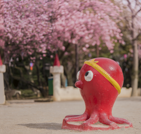 Funny red octopus sculpture looking at the cherry blossoms of Asukayama Park in the Kita district, north of Tokyo. 에디토리얼