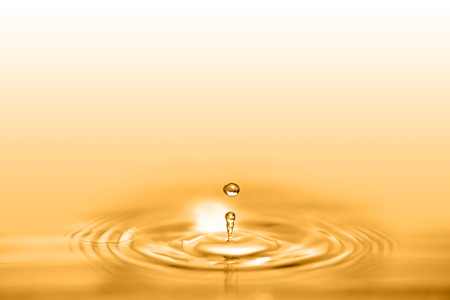 Closeup on drop of cosmetic golden oil liquid creating a circular wave.