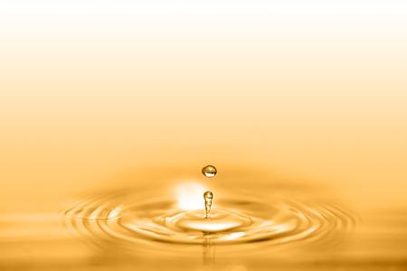 Nahaufnahme auf Tropfen der kosmetischen goldenen Ölflüssigkeit, die eine kreisförmige Welle erzeugt.