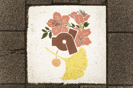 Ceramic tile decorated with cherry blossoms, cherries and leaves of Ginkgo biloba symbol of the city of Tokyo with in its center the coat of arms of the district of Bunkyo which represents the ideogram Bun of stylized way.