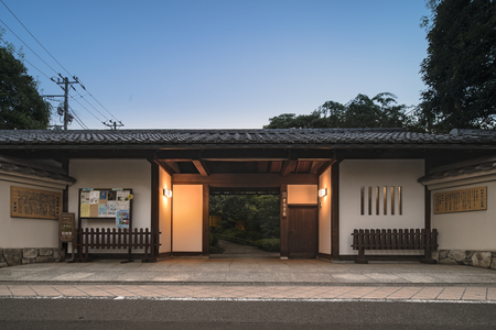 Front gate in longhouse-style of Mejiro Garden with white lacquered walls.