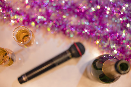Top view of romantic couple of champagne flutes and bottle of sparkling wine with black karaoke microphone and pink garland decoration for a wedding anniversary party.