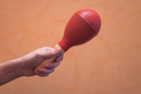 Close-up of a man's hand holding a red maraca on an orange background. 版權商用圖片