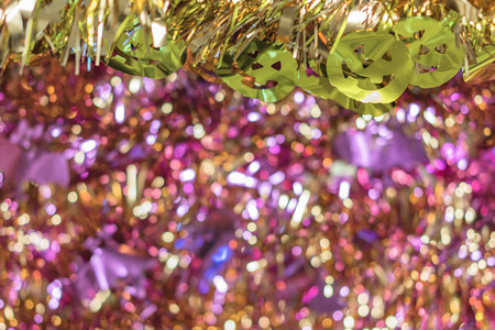 Background texture full of purple bokeh with golden garlands decorated by funny jack-o'-lantern pumpkin smiling faces decorations in foreground to celebrate the halloween party.