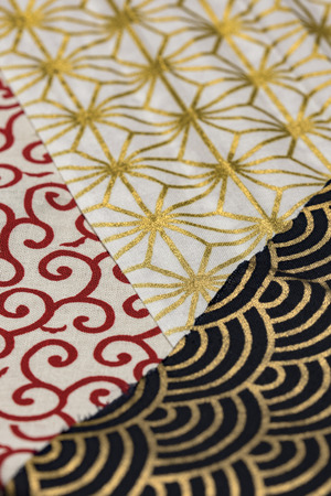 Highly detailed all over background texture of traditionals japaneses red, gold and white and black hemp leaves or rainbow  shaped pattern design textile in synthetic fabric.