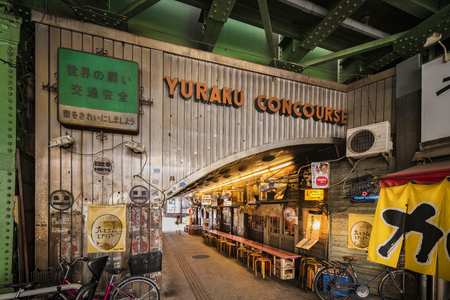 Underpass Yurakucho Concourse under the railway line of the station Yurakucho. Japanese noodle stalls and sake bars revive the nostalgic years of Showa air with old posters and placards glued to the walls of the tunnel.