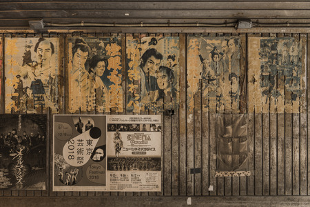 Old vintage retro japanese movie posters on underpass Yurakucho Concourse wall under the railway line of the station Yurakucho. Japanese noodle stalls and sake bars revive the nostalgic years of Showa air with old samurai posters and placards glued to the Editorial