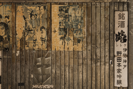 Old vintage retro japanese samurai movie posters and rusty metal advertising sign of old sake brand on underpass Yurakucho Concourse wall under the railway line of the station Yurakucho. Japanese noodle stalls and sake bars revive the nostalgic years of S
